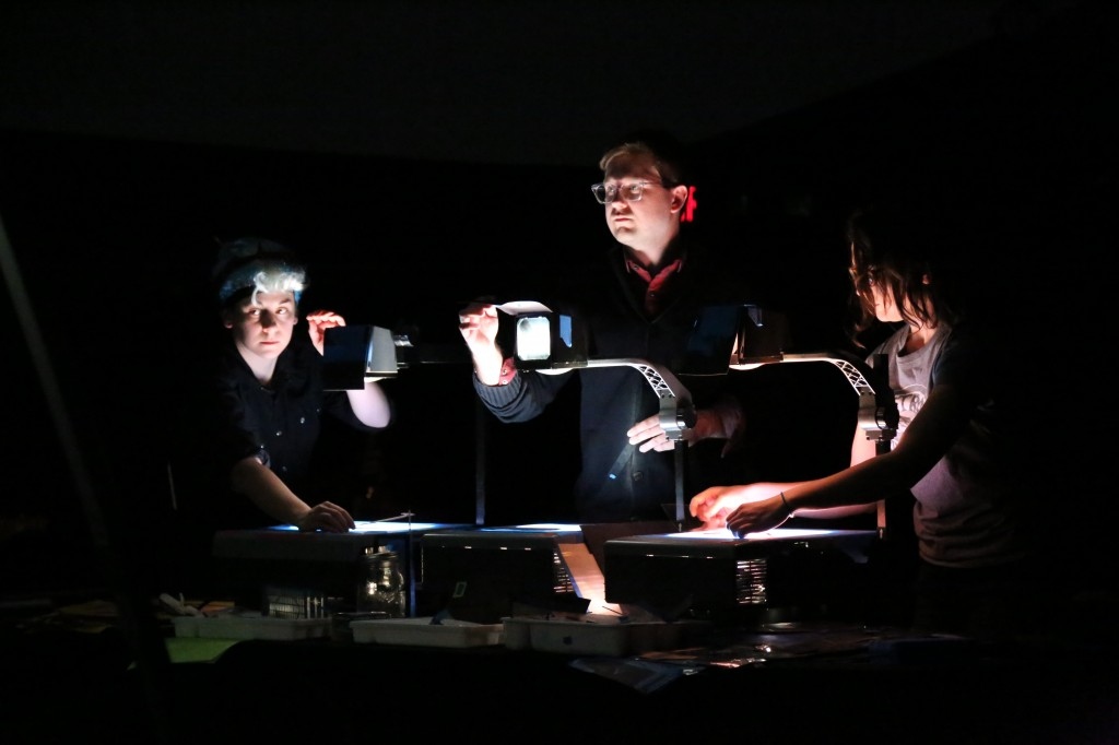 """Julia Miller, left, and Drew Dir, center, manipulate the black flaps on their projectors to """"cut"""" between scenes. Photo by Eric Krupke/NewsHour"""